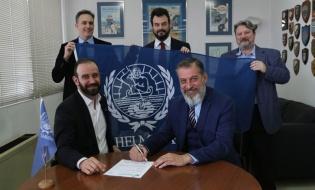 O Πλοίαρχος Νικ. Παγώνης παραδίδει τις υπογεγραμμένες αιτήσεις εγγραφής στον κ. Μιχ. Δαλακούρα με φόντο τη σημαία της HELMEPA και τoυς (αριστερά προς δεξιά) Κώστα Τριανταφύλλου, Assistant Executive Coordinator και Δημήτρη Γιάκο, Membership Services της HELMEPA  και τον Πλοίαρχο Γεράσιμο Λυμπεράτο